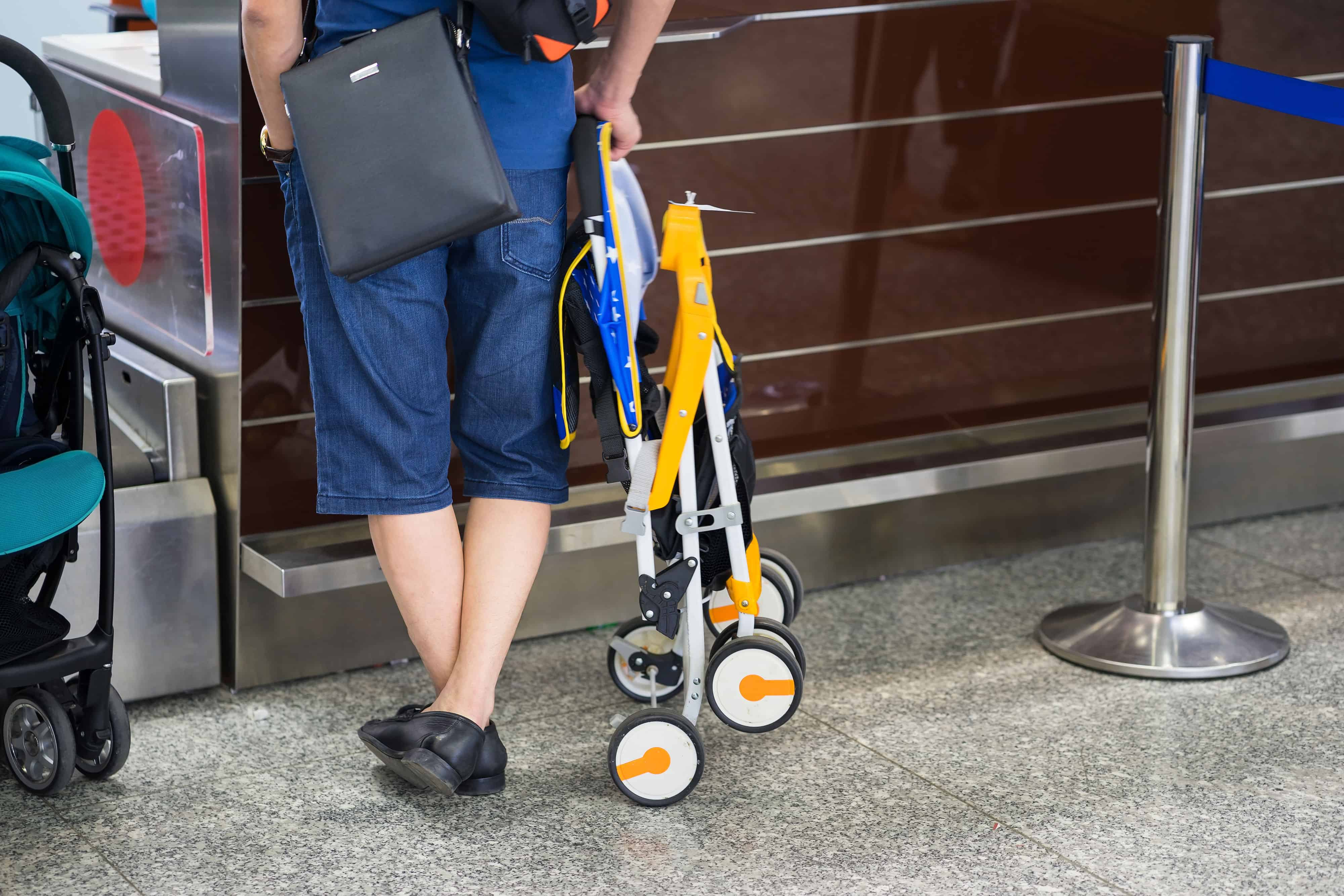 man checking into the airport with a folded stroller
