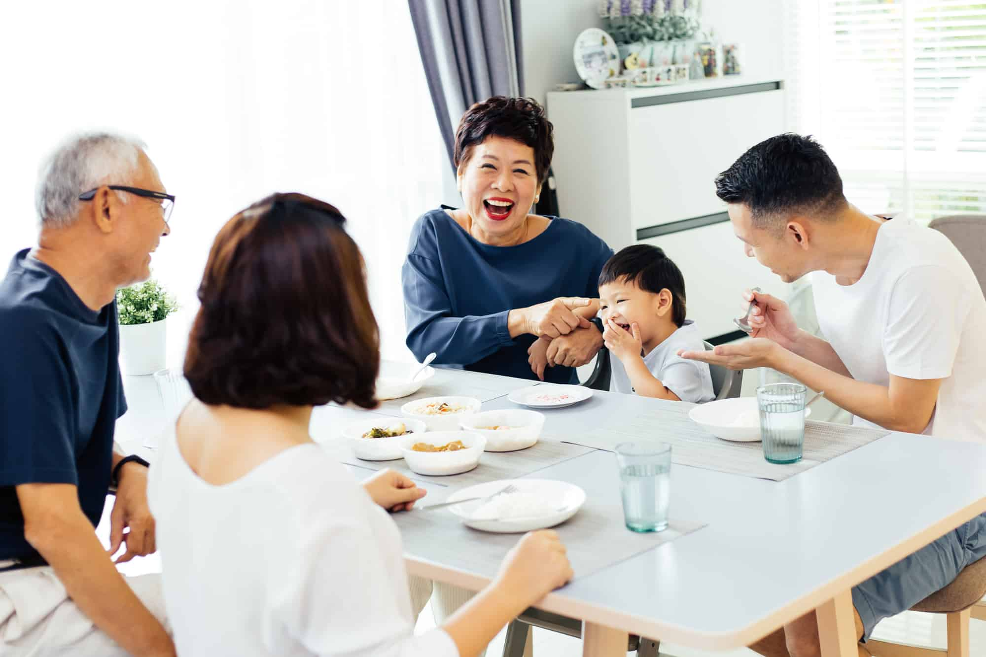 asian family sitting at dinner table