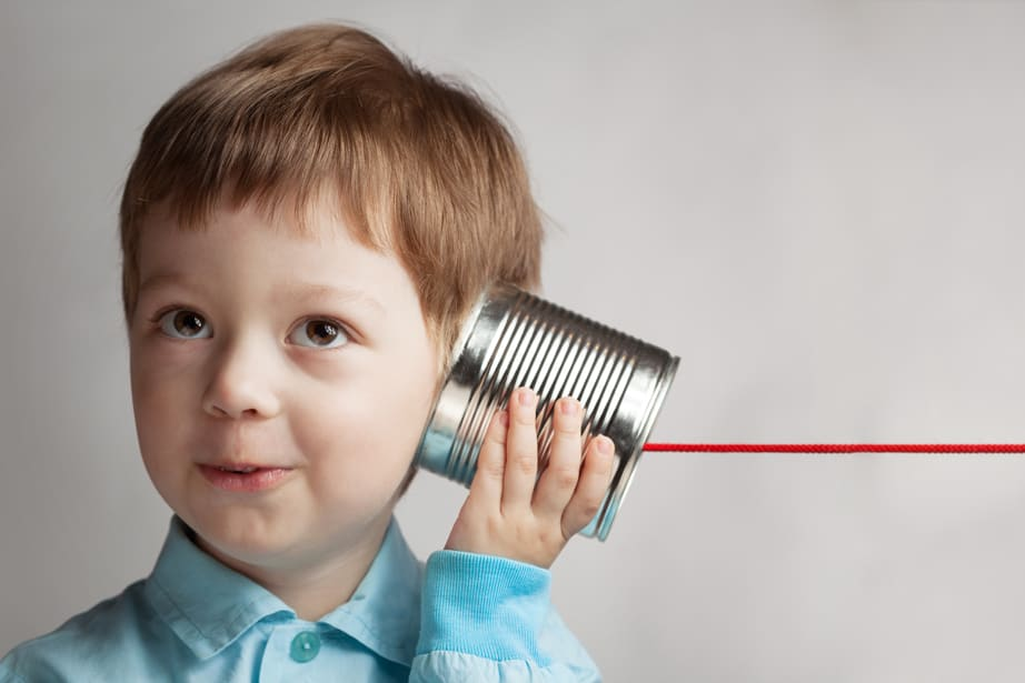 boy listening to family vacation secret with can phone on a string