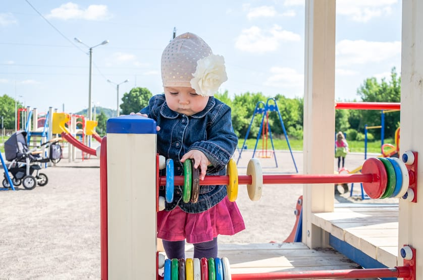 little girl playing at playground on a pit stop for family vacation