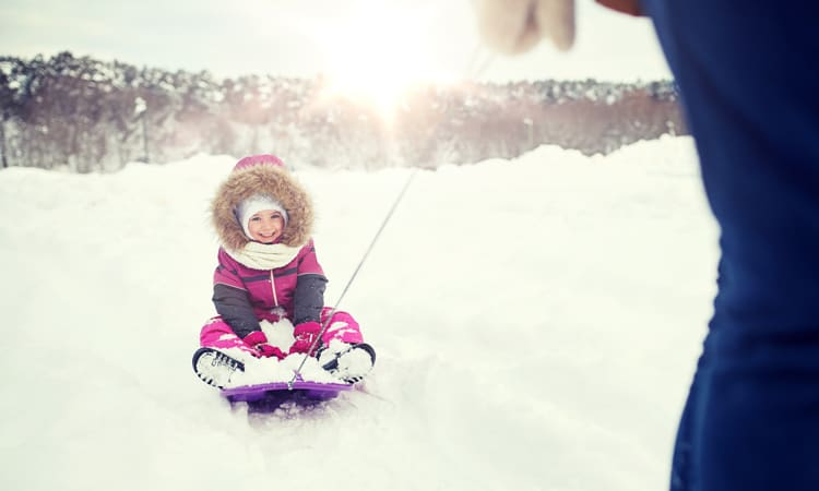 girl sledding on a cold family vacation