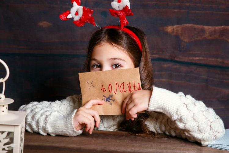 little girl holding her letter to santa