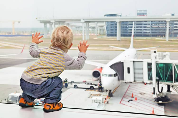 little boy looking out the window or airport at a popular airline on runway