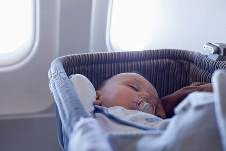 parents following airline rules on airplane with sleeping baby