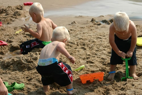 boys playing in the sand for a fun staycation