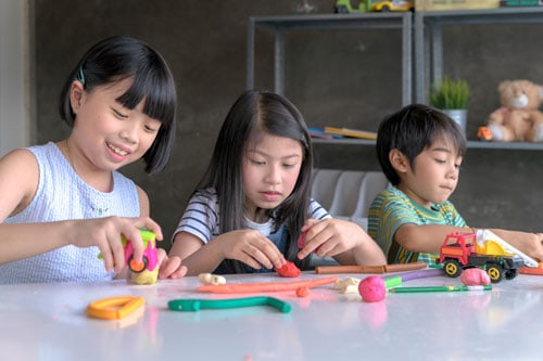 kids playing play-doh during a staycation
