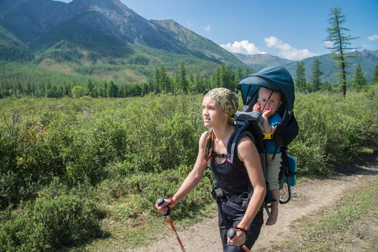woman backpacking with child