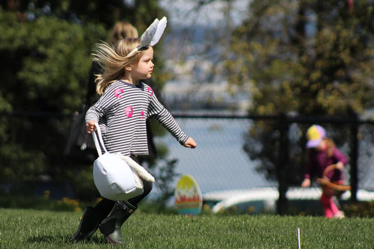 girl running after eggs on an easter egg hunt