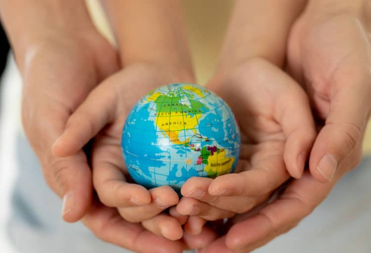 mom and baby holding globe in their hands for sustainable travel