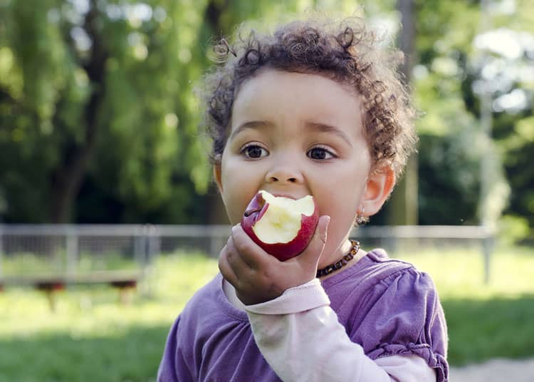 baby eating an apple for an easy travel snack