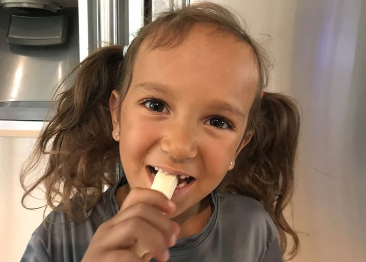 girl eating travel snack - string cheese