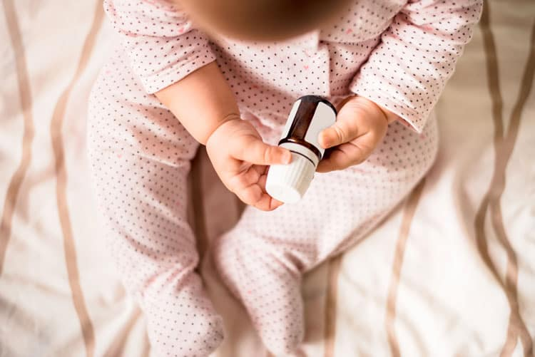 child holding a bottle of essential oils