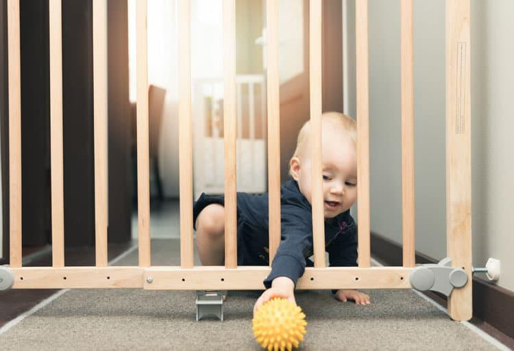 baby playing near baby gate