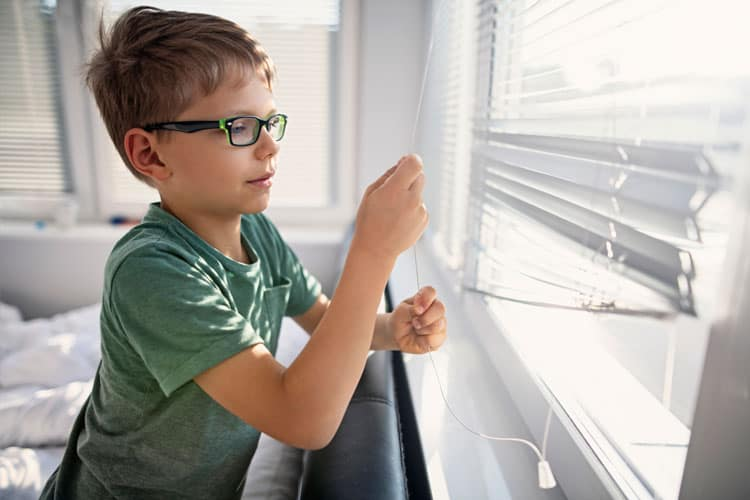 boy opening the blinds