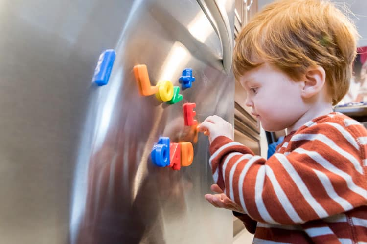 boy playing with magnets on the refrigerator