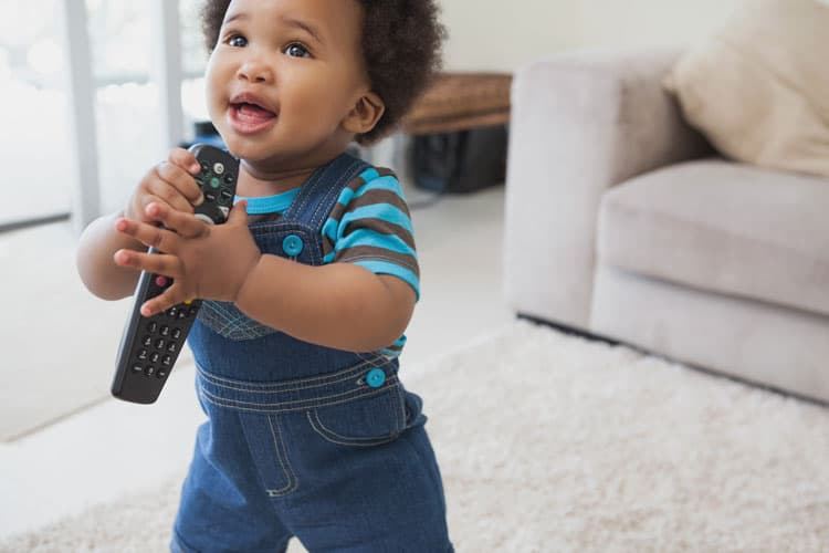 baby holding tv remote