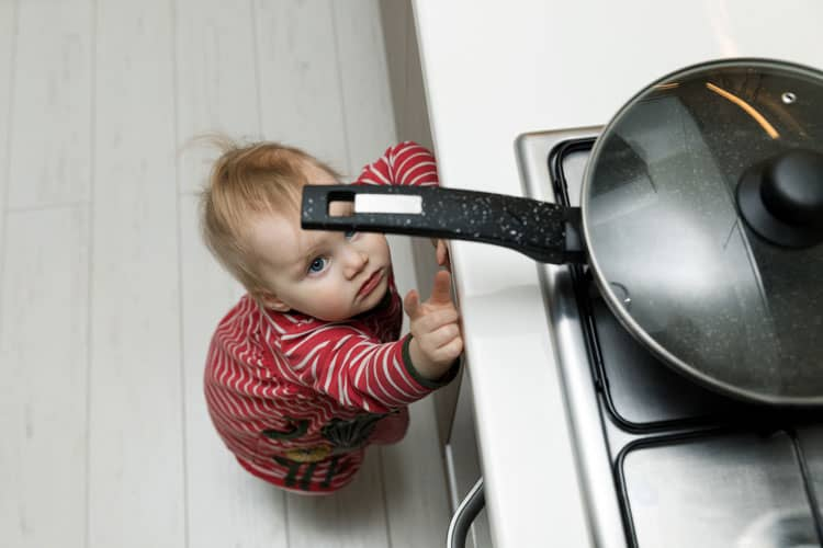 baby reaching for a hot pan on the stovetop